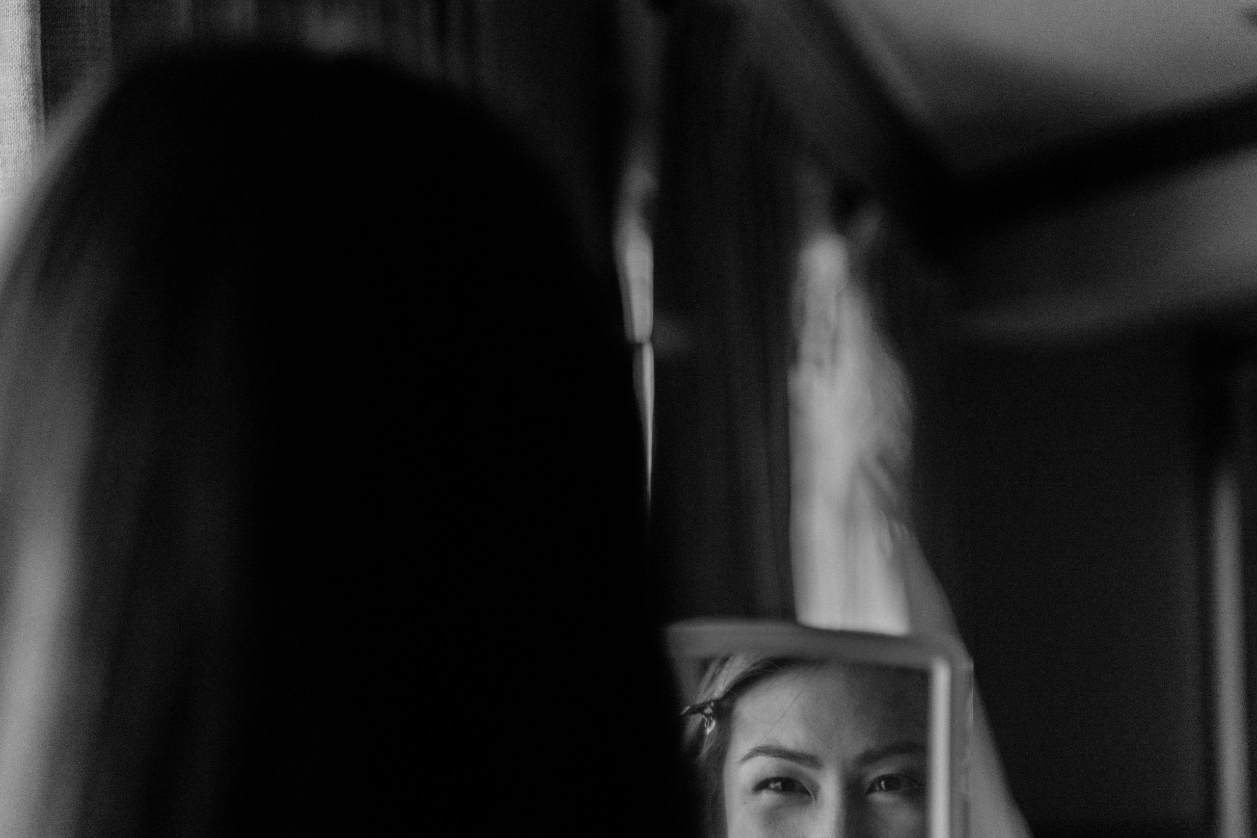 bride admires her earrings in mirror at edgewater hotel