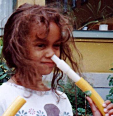 Flicka spelar flöjt med näsan