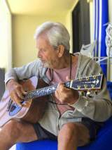 An older man playing the guitar enhances his mental health through music therapy