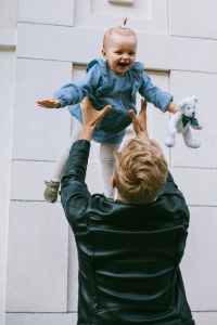 the back side of a male-appearing person playfully tossing a baby in the air. the baby is smiling. the attachment relationship you developed in early childhood influences how you relate to others.