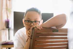 boy in white shirt wearing black framed eyeglasses. He is sitting with his face towards the back of the chair and looks lonely or sad.