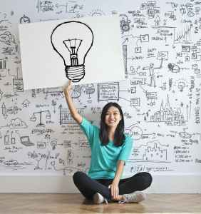 A woman of Asian ethnicity is sitting on the floor holding up an image of a lightbulb. On the wall behind her are different images representing ideas, plans, and ways of organizing information. Music therapy is one way to work with executive functioning.