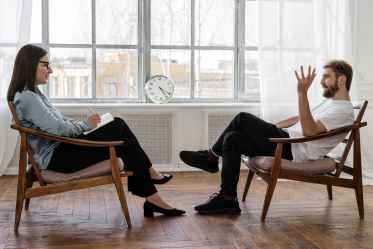 A female-presenting therapist and a male-presenting client are seated across from each other and have a good therapeutic relationship