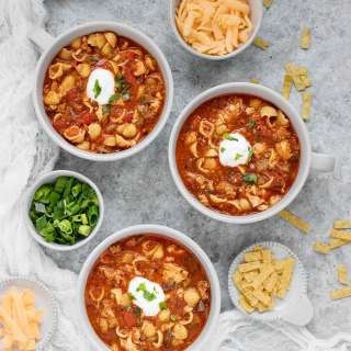 Three bowls of chicken chili soup, with toppings on the side