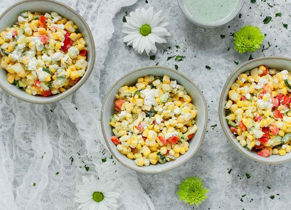 Three bowls of Sweet Corn Salad with Creamy Dill Dressing on the side