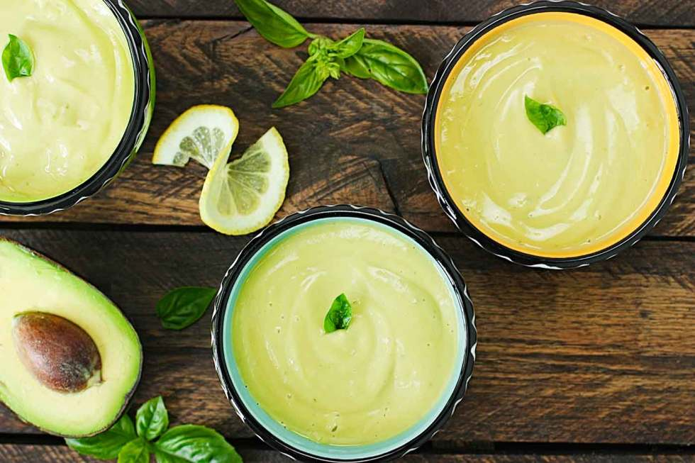 Three bowls of lemon basil avocado soup on a wooden table