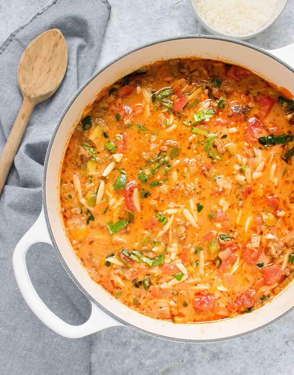 Italian Sausage Orzo Soup in a white Dutch oven with a wooden spoon