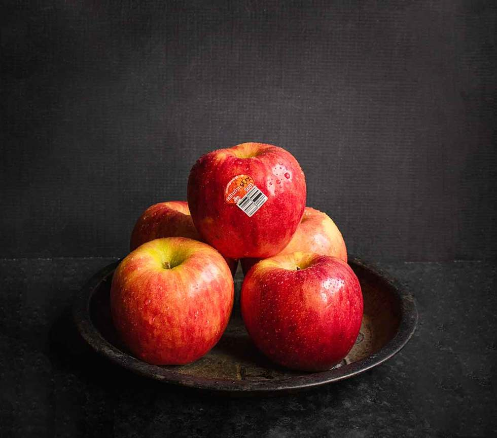 Fresh Autumn Glory apples stacked in a pyramid on a rustic tin with a blackground