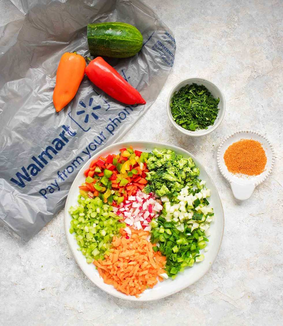 A rainbow of chopped veggies on a plate, ready to top the Ranch Veggie Pizza Appetizer