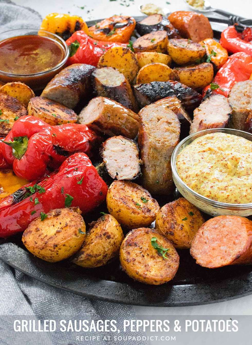 Grilled Sausages, Peppers & Potatoes on a platter with dipping sauces