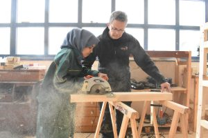 Young refugee woman uses tools in the wood workshop of makerspace Habibi.Works