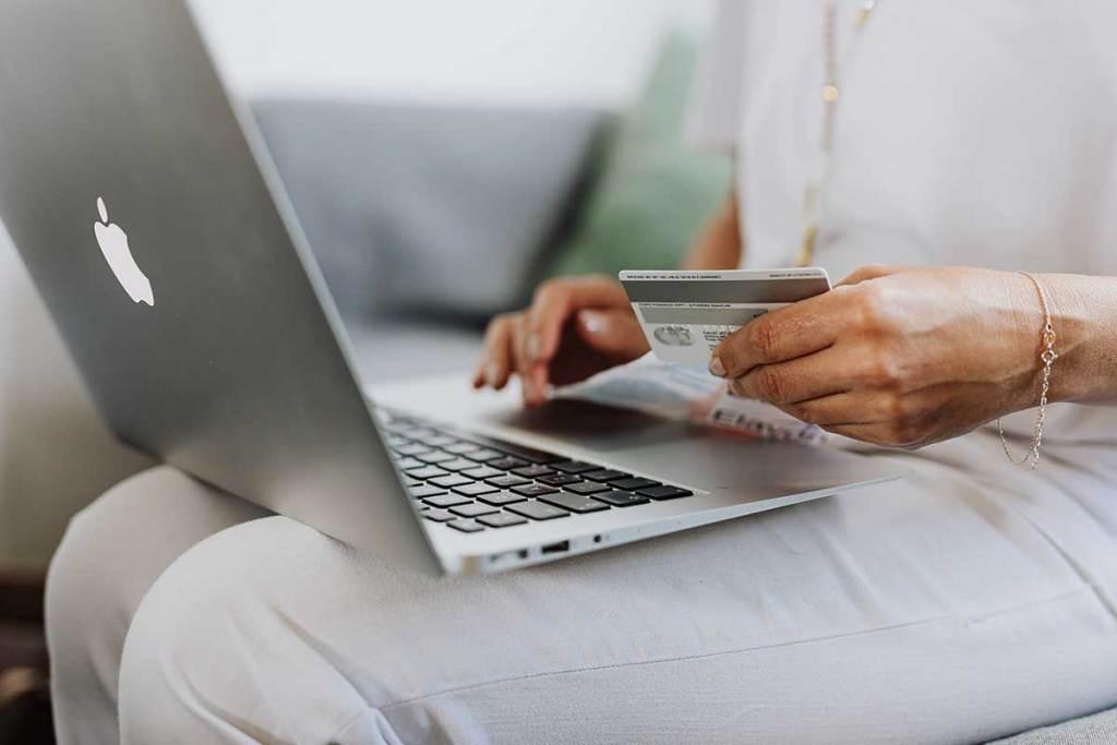 Mulher a usar um macbook e a segurar um cartão de crédito
