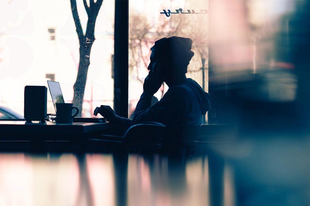 Rapaz sentado à frente do laptop