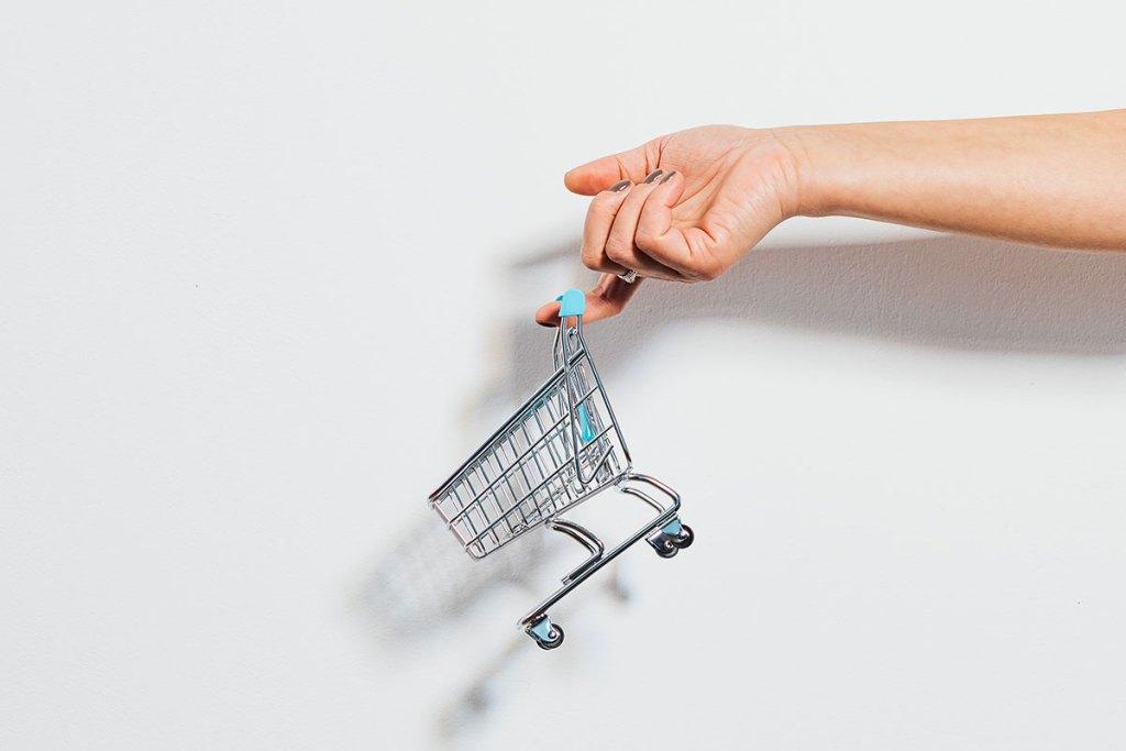 Mão a segurar um carrinho de compras