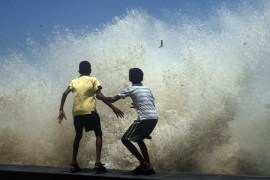 Boys get wet by the lashing waves during high tide at worli sea face promenade in Mumbai, India.