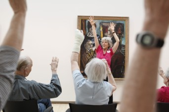 Alice Bloch leads Alzheimer's patients and caregivers through a series of light exercises during Kemper Art Reaches Everyone (KARE), a new program sponsored by WUSTL's Mildred Lane Kemper Art Museum, in collaboration with Maturity and Its Muse. (Photo: Whitney Curtis/Washington University)