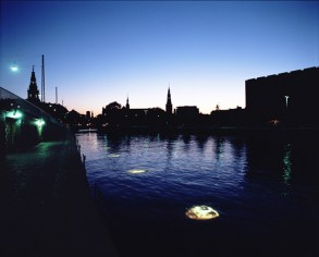 "Shimon Attie, ""Portraits of Exile, installation view, 1995. 30""X36"" , chromogenic photograph of nine 2 X 1.75 meter light boxes mounted with ""dura-trans"" photographs submerged 1 meter under water, Borsgraven Canal, Copenhagen, Denmark."