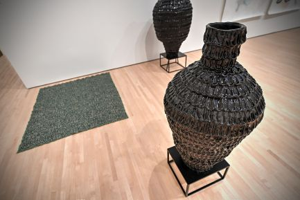 """Kahlil Robert Irving, """"Soul Sitter: Quell"""" and """"Stand: Soul Sitter,"""" both 2017. Glazed stoneware and steel. Also pictured is """"Cynodon dactylon (Devil's Grass),"""" 2017. Jacquard weaving. (Photo: James Byard/Washington University)"""