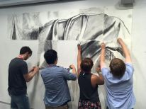 four students hang pieces of a charcoal drawing on a wall