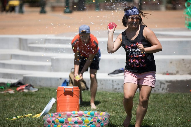 two students hold water balloons ready to toss as they get sprayed with water