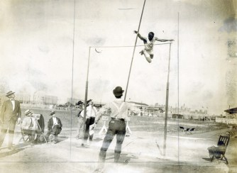 The pole vault on Francis Field. Note that in the deep background of the mid-lower right corner, you can see the twin towers of Brookings Hall, a flag waving atop each one. (Photo: Courtesy of Missouri Historical Society)