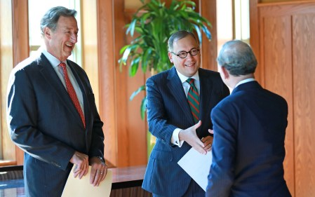 Andrew D. Martin (center) greets Chancellor Mark S. Wrighton while Craig D. Schnuck, chair of the Board of Trustees and of the chancellor search committee, looks on. (Photo: James Byard/Washington University)