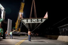 A crew from Tarlton Corp. places a span on piers Aug. 4 for the new Forest Park Parkway pedestrian bridge. (Photo: Whitney Curtis/Washington University)