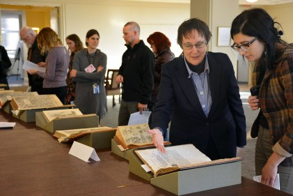Librarian Martha Riley (second from right) shows Bartolomeo Eustachi's Tabulae anatomicae, published in Amsterdam in 1722, to a visitor at Becker Medical Library's Annual Display of Rare Anatomical Texts on Dec. 5. (Photo: Laura Swofford)