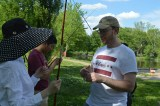 Jason Marquart, a senior adviser for the International Office of Students and Scholars, shows students how to fish at Forest Park. (Courtesy photo)
