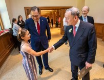 Olive Martin (left), daughter of Chancellor Andrew Martin (second left), shakes hands with former Chancellor Mark Wrighton at the dedication for Mark S. Wrighton Hall on May 31. (Photo: Joe Angeles/Washington University)