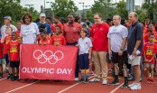 Olympian Jackie Joyner-Kersee (left), Athletics Director Anthony Azama, Chancellor Andrew D. Martin (third from right), his daughter Olive, Paralympian Steve Cash and many others join together June 21 to celebrate Olympic Day on Francis Field before walking the track. (Photo: Joe Angeles/ Washington University)