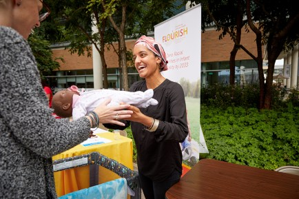 Maleeha Ahmad hands an infant doll to an individual.