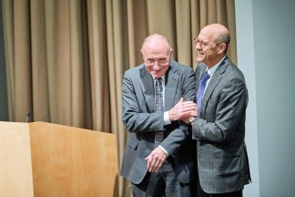 Dean David Perlmutter embraces Philip Needleman on stage.