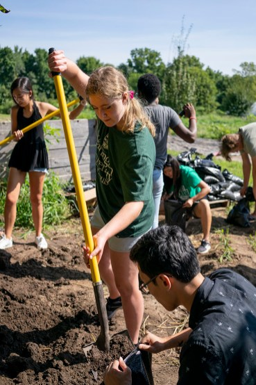 First-Year student shovels dirt into bag in a garden.