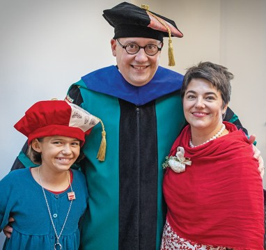 Chancellor Martin, his wife, Stephanie, and their daughter, Olive, share a relaxed moment while robing for the inauguration ceremony. Chancellor Martin and Olive are wearing custom tams (the distinctive head covering typically seen as part of academic regalia) designed by senior Meredith Liu, a fashion design major in the Sam Fox School of Design & Visual Arts. Liu. (Photo: Joe Angeles/Washington University)