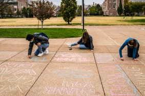 First-year students Simon Baek (left), Sarah Rosen and Olivia Danner write thank-you notes to Dining Services staff with sidewalk chalk Oct. 19 outside the Danforth University Center. (Photo: Whitney Curtis/Washington University)