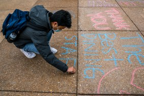 First-year student Simon Baek adds to the series of thank-you messages to Dining Services staff outside the Danforth University Center on Oct. 19. (Photo: Whitney Curtis/Washington University)