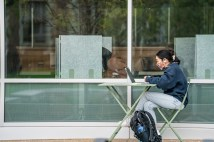 A student works at a computer outside Olin Library's Whispers Cafe at one of many new outdoor seating areas. (Photo: Whitney Curtis/Washington University)