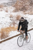 student bicycling during snowfall