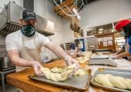 Jivan Harbian prepares bread. Bon Appetit chefs are developing recipes using Bridge Bread's array of baked goods. (Photo: Joe Angeles/Washington University)