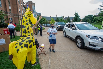 Lilly Gonzalez, residential adviser in Beaumont Hall, dresses as a giraffe to welcome students and their families to the South 40 on Move-in Day Aug. 21. (Photo: Joe Angeles/Washington University)