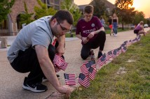 WashU students Cole Chavez (left) and George Andreescu place miniature American flags around Mudd Field on Sept. 10. (Photo: Sid Hastings/Washington University)