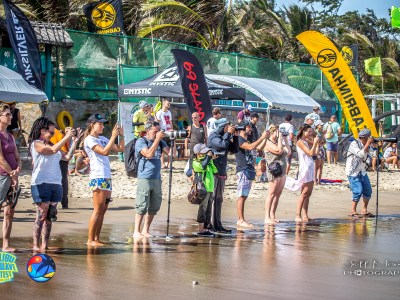 line of photographers taking shots at kitesurf competition