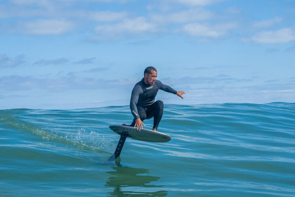 man in wetsuit riding north foil board