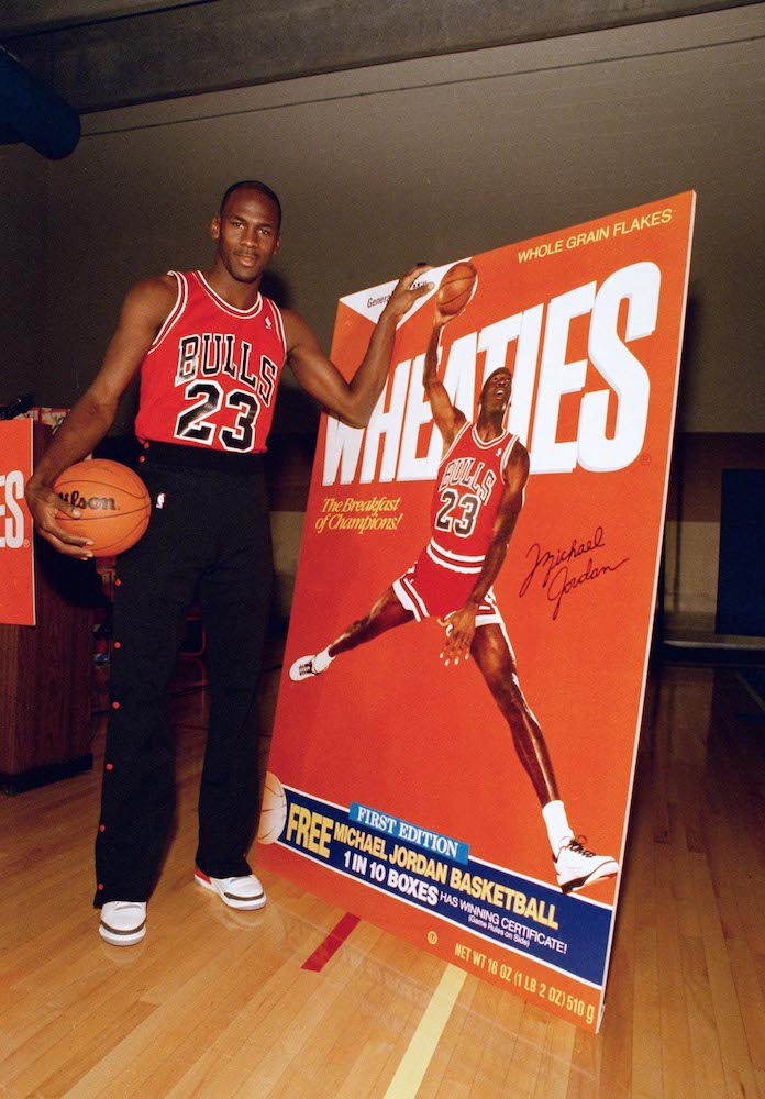"Michael Jordan poses alongside his likeness on a box of Wheaties during an unveiling ceremony in Chicago, . Jordan is the seventh celebrity athlete to have his image displayed on a box of the cereal marketed as ""The Breakfast of Champions<br /> Bulls Jordan Wheaties 1988, Chicago, USA"