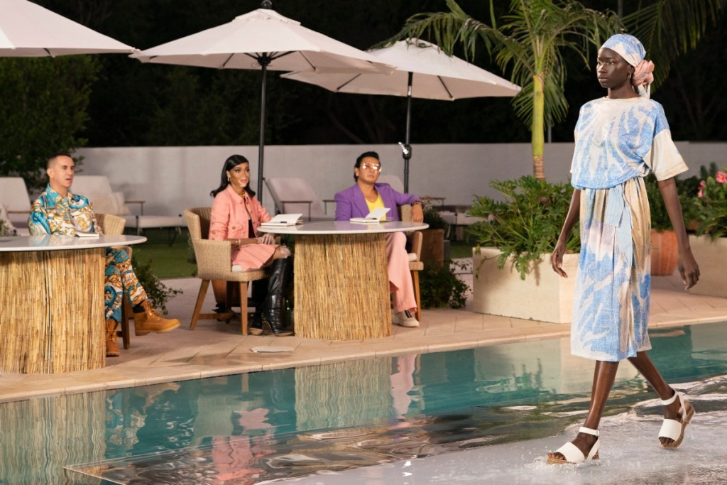"""Regular judges Jeremy Scott and Winnie Harlow, along with Prabal Gurung appearing in a guest role, watching Gary Graham's resortwear looks come down the water-filled catwalk in episode two of """"Making the Cut"""" on Amazon Prime Video."""