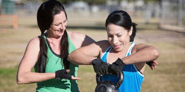 Friendly fitness instructor helping student use kettle bell weight