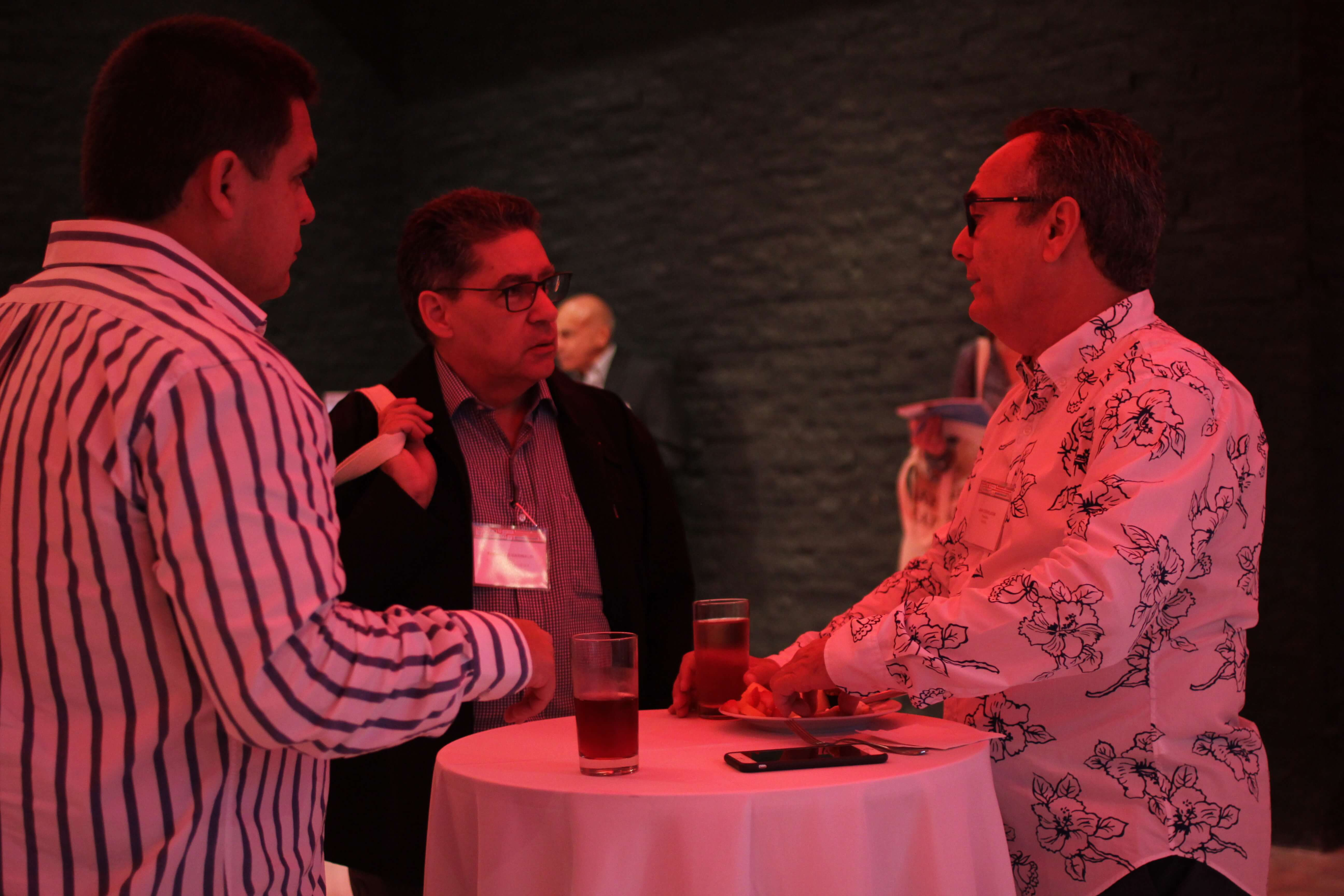 Three men chatting with drinks