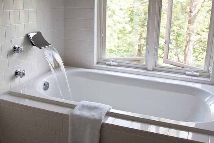 A Deep relaxing tub by an open window filling with water