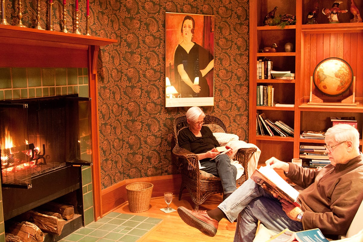An older couple reads together by the fire